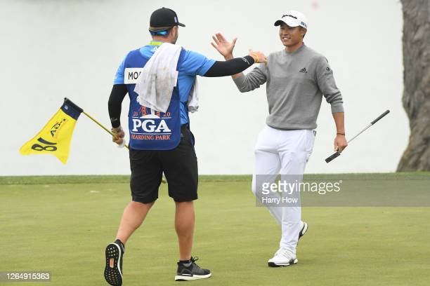Collin Morikawa of the United States celebrates making his final putt on the 18th green with caddie Jonathan Jakovac during the final round of the...