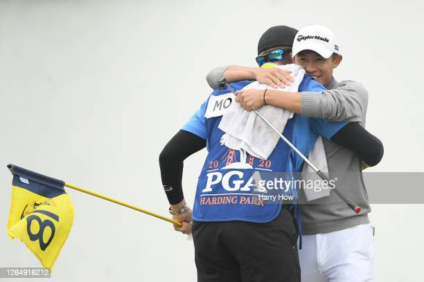 Collin Morikawa of the United States celebrates with caddie Jonathan Jakovac after making his final putt on the 18th green during the final round of...