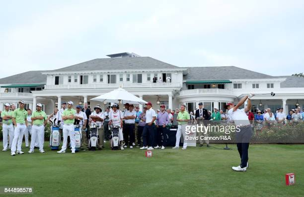 Collin Morikawa of the United States team hits the first tee shot of the matches in his match with Norman Xiong against Alfie Plant and Harry Ellis...