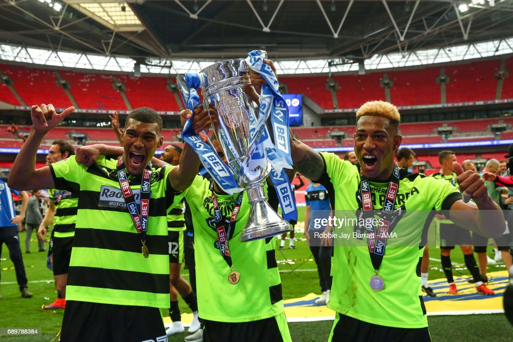 Collin Quaner of Huddersfield Town and Rajiv Van La Parra of Huddersfield Town celebrate with the Sky Bet Championship Play off final trophy during the Sky Bet Championship Play Off Final match between Reading and Huddersfield Town at Wembley Stadium on May 29, 2017 in London, England.