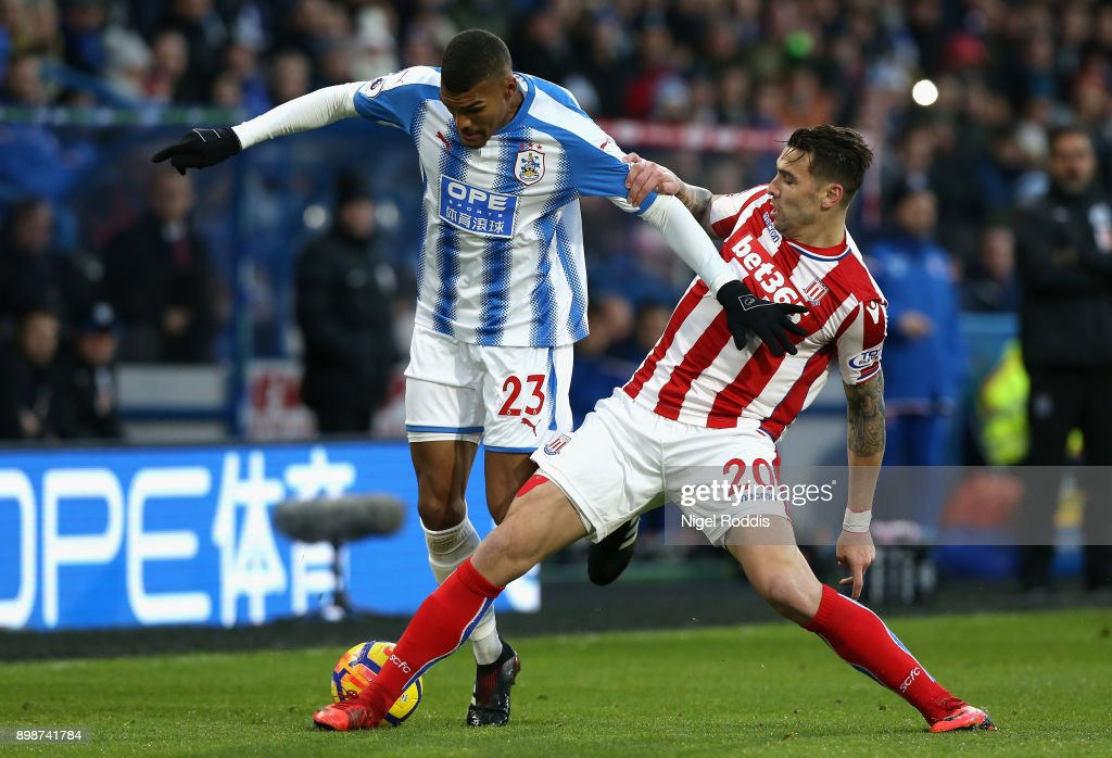 Collin Quaner of Huddersfield Town battles for possesion with Geoff Cameron of Stoke City during the Premier League match between Huddersfield Town and Stoke City at John Smith's Stadium on December 26, 2017 in Huddersfield, England.