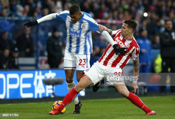 Collin Quaner of Huddersfield Town battles for possesion with Geoff Cameron of Stoke City during the Premier League match between Huddersfield Town...