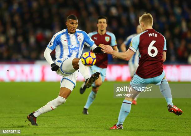 Collin Quaner of Huddersfield Town is challenged by Ben Mee of Burnley during the Premier League match between Huddersfield Town and Burnley at John...