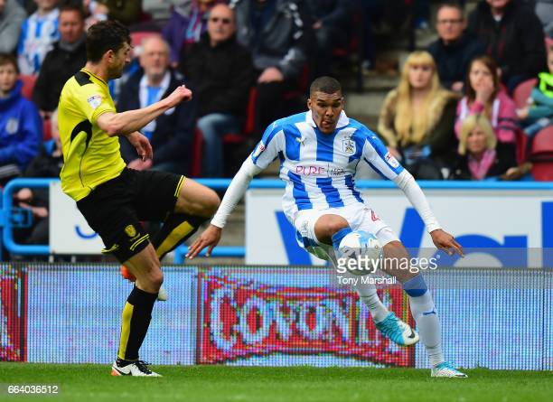 Collin Quaner of Huddersfield Town is tackled by John Mousinho of Burton Albion during the Sky Bet Championship match between Huddersfield Town and...