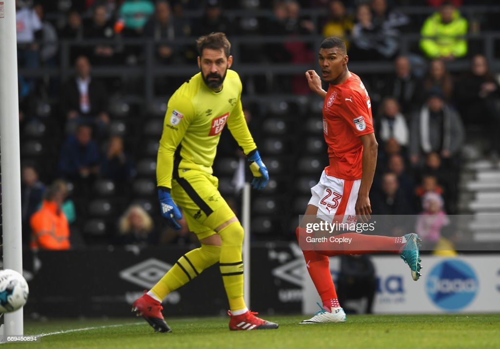 Collin Quaner of Huddersfield Town scores the opening goal past Scott Carson of Derby County during the Sky Bet Championship match between Derby County and Huddersfield Town at iPro Stadium on April 17, 2017 in Derby, England.
