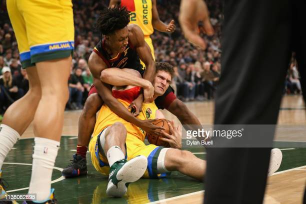 Collin Sexton of the Cleveland Cavaliers and Brook Lopez of the Milwaukee Bucks battle for a loose ball in the first quarter at the Fiserv Forum on...