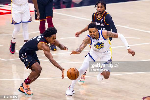 Collin Sexton of the Cleveland Cavaliers and Kent Bazemore of the Golden State Warriors reach for the ball at Rocket Mortgage Fieldhouse on April 15,...