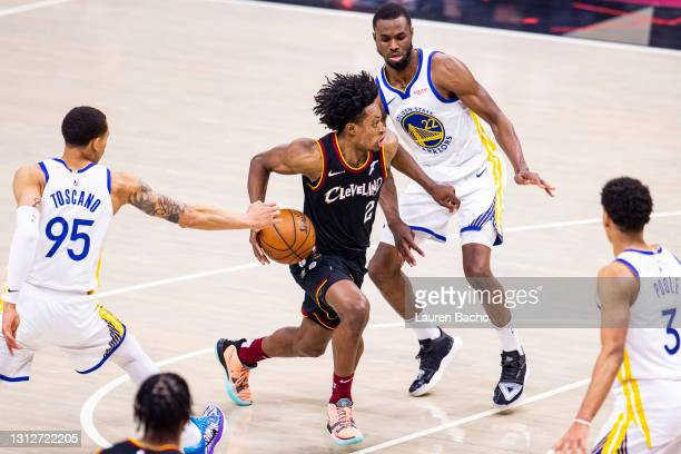 Collin Sexton of the Cleveland Cavaliers dribbles towards the basket against Juan Toscano-Anderson and Andrew Wiggins of the Golden State Warriors...