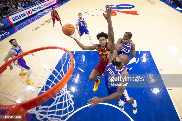 Collin Sexton of the Cleveland Cavaliers goes up for a shot against Kyle O'Quinn and James Ennis III of the Philadelphia 76ers in the second quarter...