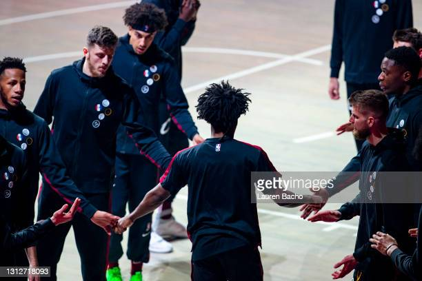 Collin Sexton of the Cleveland Cavaliers high fives his teammates as the starting lineup is announced before the game against the Golden State...