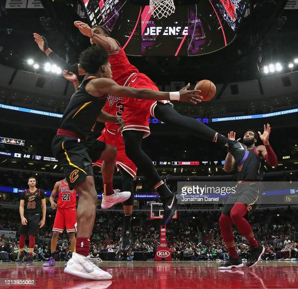 Collin Sexton of the Cleveland Cavaliers passes around Daniel Gafford of the Chicago Bulls to teammate Andre Drummond at the United Center on March...