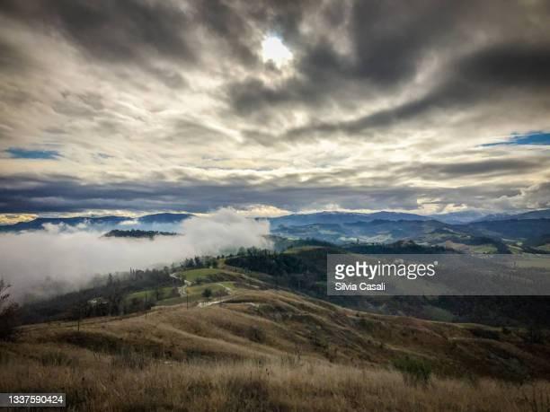 colline in inverno con nuvole basse e cielo minaccioso - silvia casali bildbanksfoton och bilder