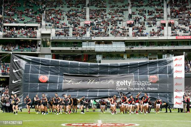 Collingwood and Essendon player run through a joint banner before during the round six AFL match between the Collingwood Magpies and the Essendon...