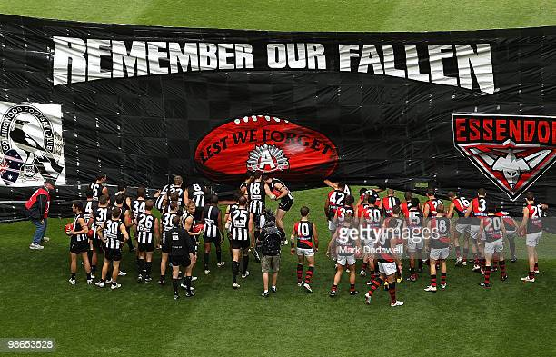 Collingwood and Essendon players run through the Anzac Day banner during the round five AFL match between the Collingwood Magpies and the Essendon...