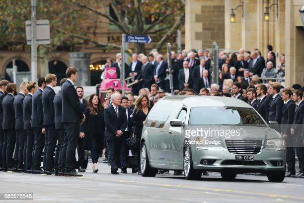 Collingwood Magpies players form a guard of honour as the coffin of Lou Richards leaves the Service in a hearse during the Lou Richards State Funeral...