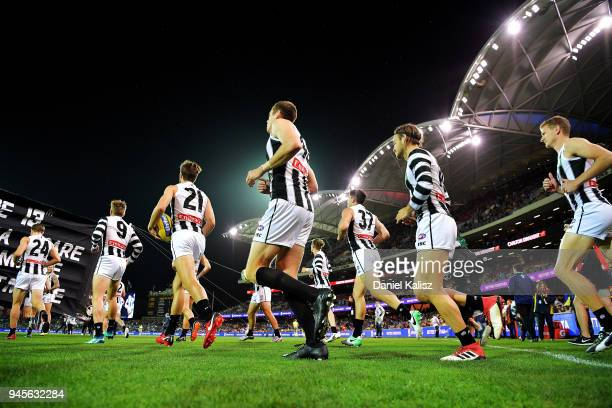 Collingwood Magpies players run onto the field prior to the round four AFL match between the Adelaide Crows and the Collingwood Magpies at Adelaide...