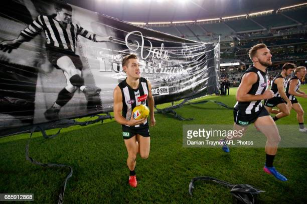 Collingwood players run through the banner before the round nine AFL match between the Collingwood Magpies and the Hawthorn Hawks at Melbourne...