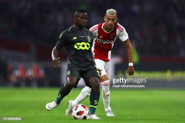 Collins Fai of Standard de Liege battles for the ball with Hakim Ziyech of Ajax during the UEFA Champions League third round qualifying match between...