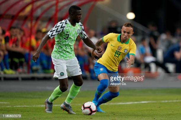 Collins Jamilu of Nigeria holds off Everton of Brazil during the international friendly match between Brazil and Nigeria at the Singapore National...