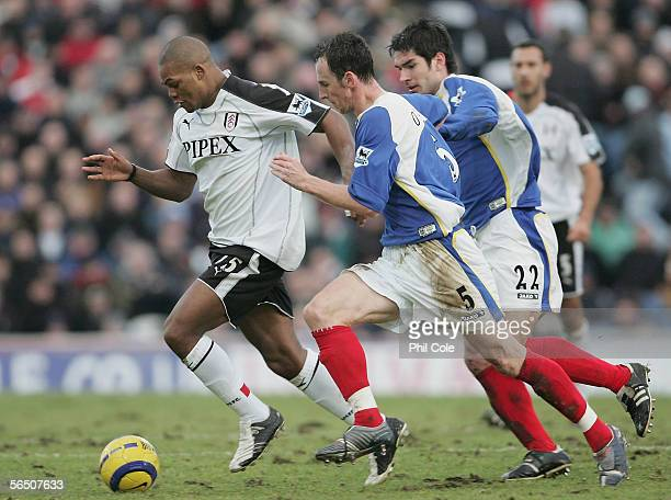 Collins John of Fulham takes on Andy O'Brien and Richard Hughes of Portsmouth during the Barclays Premiership match between Portsmouth and Fulham at...