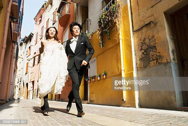 Collioure, France, bride and groom running through streets