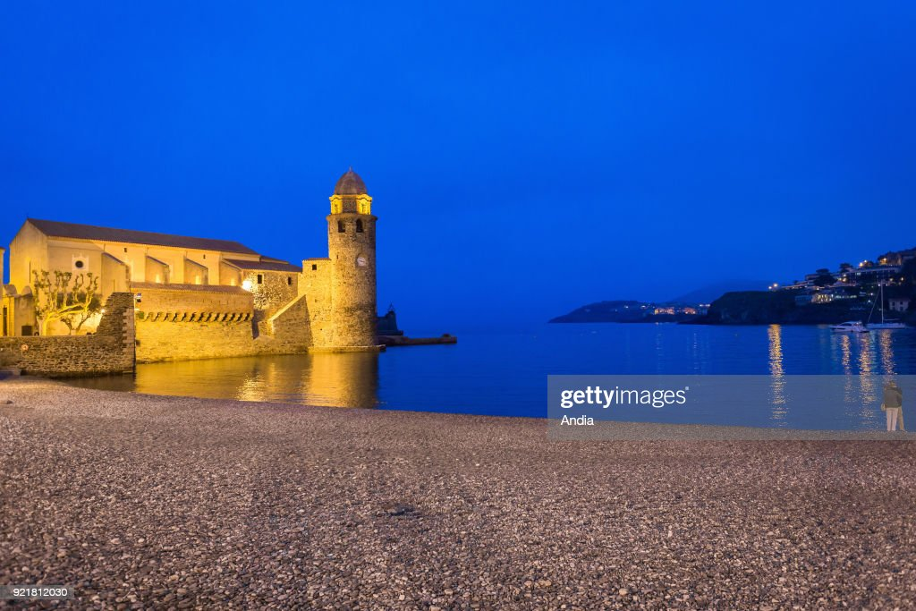 Collioure (south of France), on : night view of the tourist town located along the 'Cote Vermeille' (Vermilion Coast). The Church of Our Lady of the Angels ('eglise paroissiale Notre Dame des Anges'), overhanging the bay, with its bell tower, emblem of the town.