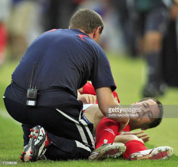 English forward Michael Owen is treated after being injured during the opening round Group B World Cup football match Sweden vs England 20 June 2006...