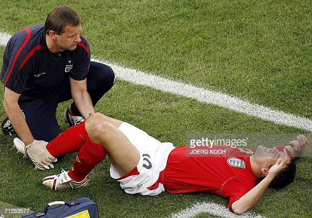 English forward Michael Owen is treated on the pitch after badly injuring his right knee uring the opening round Group B World Cup football match...