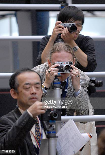 Fairgoers try out Leica cameras at the Photokina trade fair in Cologne 26 September 2006 The world's largest trade fair for camera equipment opens...