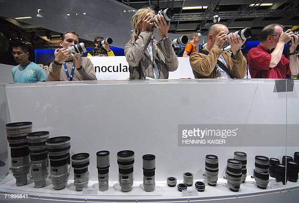 Fair-goers try out lenses Japanese manufacturer Canon at the Photokina trade fair in Cologne 26 September 2006. The world's largest trade fair for...