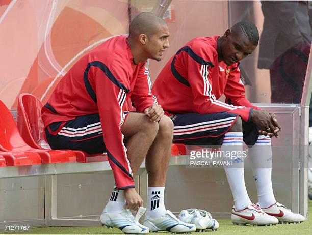 French David Trezeguet and defender Eric Abidal sit on a bench during a training session fat the Cologne stadium 22 June 2006 on the eve of their...