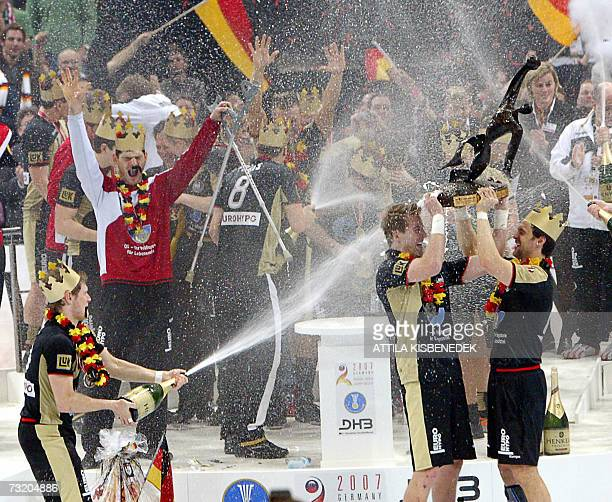 German Oliver Roggisch lifts the trophy as teammates spill champagne on him during the awards ceremony after Germany defeated Poland in the final of...