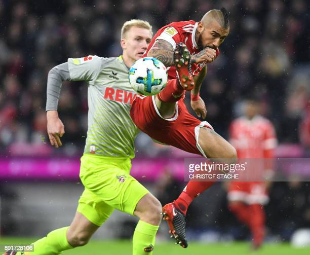 Cologne's Danish defender Frederik Soerensen and Bayern Munich's Chilian midfielder Arturo Vidal vie for the ball during the German first division...
