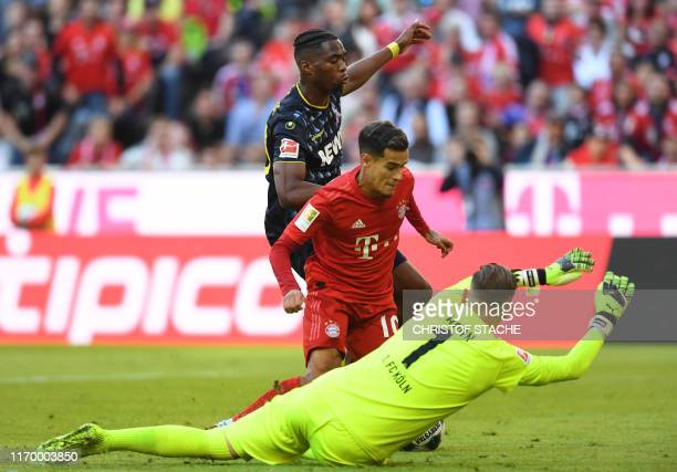 Cologne's Dutch defender Kingsley Ehizibue attacks Bayern Munich's Brazilian midfielder Philippe Coutinho as Cologne's German goalkeeper Timo Horn...
