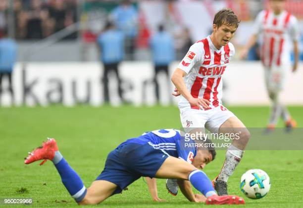 Cologne's French midfielder Vincent Koziello and Schalke's French midfielder Amine Harit vie for the ball during the German first division Bundesliga...