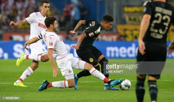 Cologne's German defender Jonas Hector and Dortmund's English midfielder Jadon Sancho vie for the ball during the German first division Bundesliga...