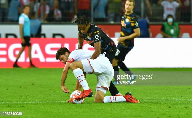 Cologne's German defender Jonas Hector and Leipzig's French midfielder Christopher Nkunku vie for the ball during the German first division...