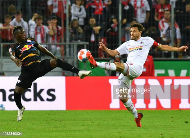 Cologne's German defender Jonas Hector and Leipzig's Malian midfielder Amadou Haidara vie for the ball during the German first division Bundesliga...