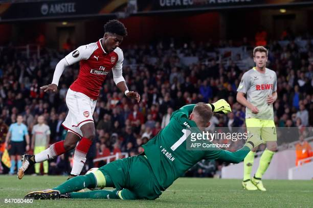FC Cologne's German goalkeeper Timo Horn dives to make a save at the feet of Arsenal's English midfielder Ainsley MaitlandNiles during the UEFA...