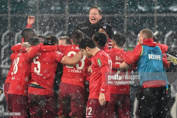 Cologne's German head coach Markus Gisdol and his players celebrate after the German first division Bundesliga football match between Borussia...