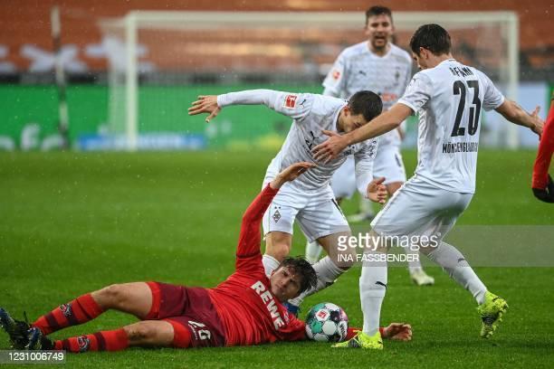 Cologne's German midfielder Elvis Rexhbecaj, Moenchengladbach's Austrian defender Stefan Lainer and Moenchengladbach's German midfielder Jonas...