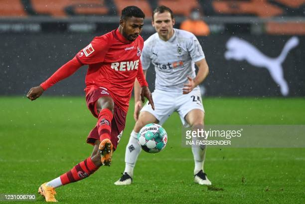 Cologne's Nigerian forward Emmanuel Dennis plays the ball in front of Moenchengladbach's German defender Tony Jantschke during the German first...