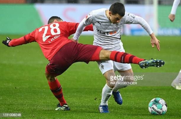 Cologne's Tunisian midfielder Ellyes Skhiri and Moenchengladbach's Austrian defender Stefan Lainer vie for the ball during the German first division...