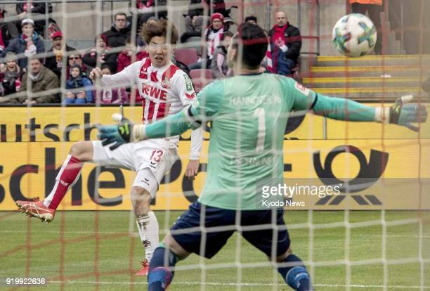 Cologne's Yuya Osako scores the opener past Hannover's keeper Philipp Tschauner during the first half of a 11 Bundesliga match draw in Cologne on Feb...