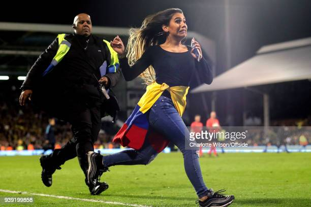 Colombia fan clearly regrets invading the pitch as she is chased by a large security guard during the International Friendly match between Australia...