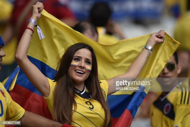 A Colombia fan holds her national flag before a Group C football match between Colombia and Greece at the Mineirao Arena in Belo Horizonte during the...