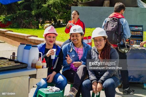 Colombia - ingenieros de señora con sombreros duros merendar carretera en la vereda en Bogotá