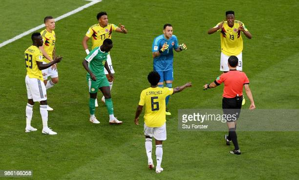 Colombia players confront referee Milorad Mazic after he awards Senegal a penalty before rescinding the decision after reviewing VAR footage during...