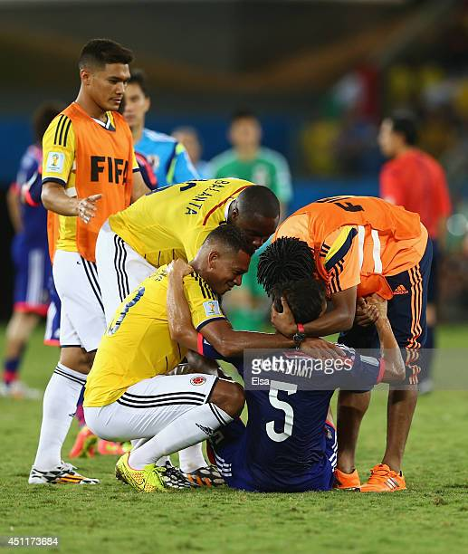 Colombia players embrace Yuto Nagatomo of Japan after the 2014 FIFA World Cup Brazil Group C match between Japan and Colombia at Arena Pantanal on...
