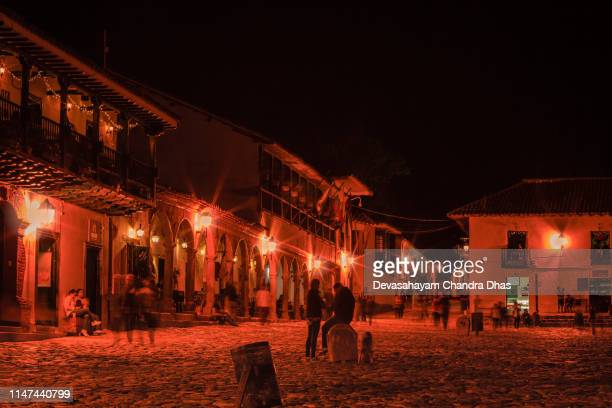 colombia, south america - tourists and some local residents on the eastern corner of the plaza mayor in the historic 16th century town of villa de leyva in the boyacá department, just after sunset; night shot lit by street lights - cafe de colombia stock pictures, royalty-free photos & images